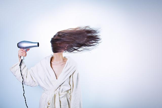 Torkar håret med hårfön
